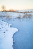 Winter sunset over frozen pond Stock Photography