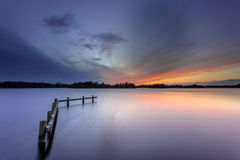 Winter Sunset over Tranquil Lake with Wooden Mooring Post Stock Photography