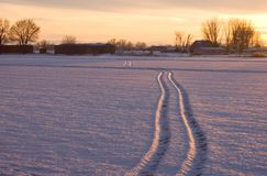 Winter sunset at the ranch. The setting sun shows off the tracks in the snow Royalty Free Stock Photos