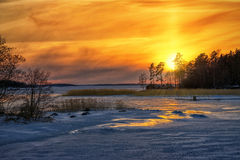 Winter sunset reflections from iced sea. With red houses in the distance - Sweden Royalty Free Stock Image