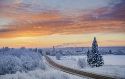 Winter sunset  road through snowy fields Stock Images