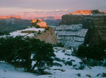 Winter sunset, Shafer Point and La Sal Mountains, Canyonlands National Park, Utah. Redrock, snow, solitude and cold temperatures combine to make winter my stock photography