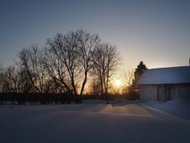 The winter sunset. The sun sets off near the barn. Photo taken in February 2015. It was a beautiful winter landscape stock images