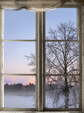 Winter sunset viewed through old window Stock Photo