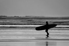 Surfer. A lone surfer walking aways from the sea after a winters surfing session Stock Images