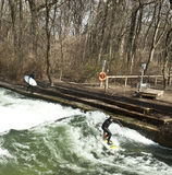 Winter surfing in diving suit on the Eisbach river at Englische stock photography