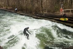 Winter surfing in diving suit on the Eisbach river at Englische stock photo