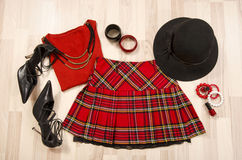 Winter sweater and plaid skirt with accessories arranged on the floor. Royalty Free Stock Photo