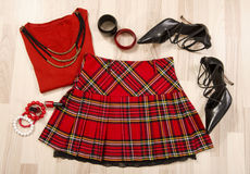 Winter sweater and plaid skirt with accessories arranged on the floor. Royalty Free Stock Photos