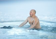 Winter swimming. Man in ice-hole Stock Photos