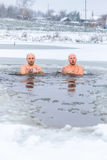 Winter swimming. Man in ice-hole. Winter swimming. Two Man in an ice-hole in outdoors royalty free stock photos