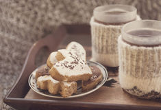 Winter tea and cookies. Tea cups in knitted covers and honey-cakes Stock Image