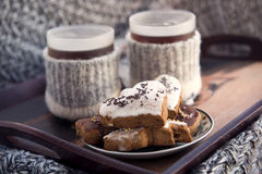 Winter tea and cookies. Tea cups in knitted covers and honey-cakes Royalty Free Stock Images