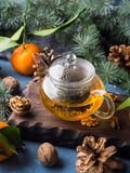 Winter tea and tangerines. Winter tea in pot and tangerines with pine cones and fir tree branches stock photo