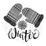 Winter text and knitted woolen mittens with snowflakes. Seasonal shopping concept for design cards or labels. Stock Photos