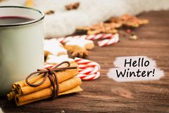 Winter theme. Hot steaming cup of glint wine with spices, cinnamon, anise, cookies in a shape of star, red candies, pepper and. Gray scarf on wooden background stock photos