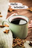 Winter theme. Hot steaming cup of glint wine with spices, cinnamon, anise, red candies, pepper and gray scarf on wooden background. With text Hello Winter. View royalty free stock photos