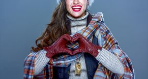 Smiling woman isolated on cold blue showing heart shaped hands. Winter things. Closeup on smiling modern woman in fur hat isolated on cold blue showing heart Royalty Free Stock Photo