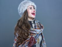 Happy elegant woman in fur hat isolated on cold blue rejoicing Royalty Free Stock Photography