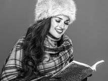 Modern woman in fur hat isolated on cold blue reading book. Winter things. Portrait of happy modern woman in fur hat isolated on cold blue reading book Stock Photos