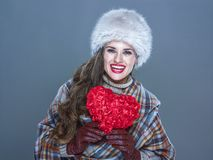 Smiling elegant woman  on cold blue with red heart. Winter things. Portrait of smiling elegant woman in fur hat  on cold blue with red heart Royalty Free Stock Image
