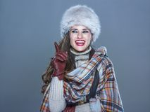 Smiling elegant woman in fur hat isolated on cold blue got idea. Winter things. Portrait of smiling elegant woman in fur hat isolated on cold blue got idea Stock Photo