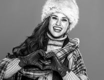 Smiling woman  on cold blue showing heart shaped hands. Winter things. Portrait of smiling modern woman in fur hat  on cold blue showing heart shaped hands Stock Photography