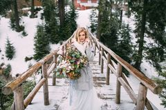 Beautiful young girl stands in winter with a bouquet of flowers in her hands Royalty Free Stock Photography