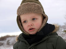 Winter time. Little boy playing outsite in the winter day stock photo