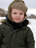 Winter time. Little boy playing outsite in the winter day royalty free stock photos