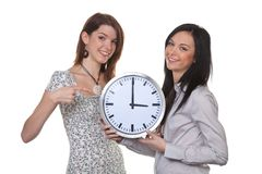 Winter time change daylight savings time. Two young girls show the new time at time changeover Stock Images