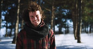 Winter time charismatic man enjoying the time in the middle of snowy forest in front of the camera smiling large he take. Some fresh air stock video footage