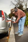 Winter time dressed man filling tank of car from canister Stock Images