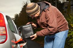Winter time dressed man filling tank of car on street Stock Photography