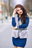 Winter time fashion for women. Woman wearing sweater fur vest belt and pendant in freezing cold time. Excellent Bright Stock Photo