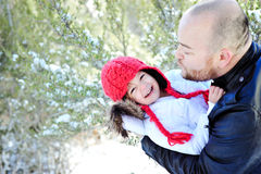 Winter Time Father and Daughter Kissing. Father and Daughter outdoors in snowy area smiling and kissing Stock Photography