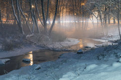 Winter-time fog over brook by night Stock Photos