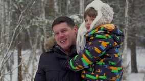 Portrait of happy father and a very cute happy little boy, his son in a snow winter park. smiling boy. Attractive family stock video footage
