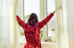 Winter time at home, young girl in winter warm pajamas with a cat looking out the window.  stock photo