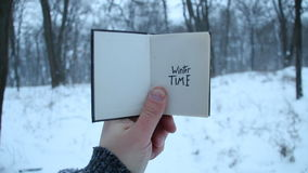 Winter time idea. Book and text. Winter time. Hand holding a book with the inscription stock video footage