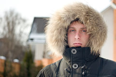 Winter time - man in warm jacket with furry hood Royalty Free Stock Image
