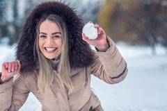 Winter time - girl playing snowball fight on the winter snow day. Winter time - Smiling girl playing snowball fight on the winter snow day stock images
