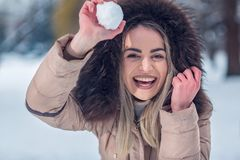 Winter time - Smiling girl playing snowball fight on the winter. Winter time - Smiling young girl playing snowball fight on the winter snow day royalty free stock images