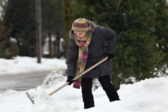 Winter time, snow removing from street. Caucasian woman cleaning snow from sidewalk using shovel, winter time Stock Photo