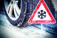 Winter time. Winter tire on a street in winter with traffic sign Royalty Free Stock Photos