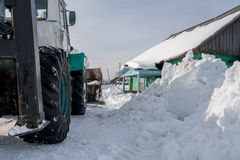 Winter time. Tractor cleans snow in village Stock Photography