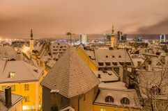 Winter time view on snowbound old town and modern city at night royalty free stock images