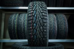 Winter tire on the background of racks with tires Royalty Free Stock Photos