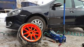 Winter tire fitting on the street. Wheel service, Tire repair, and changing summer to winter tires. Black car lifted on jack. Summer tires in winter. Orange royalty free stock photography