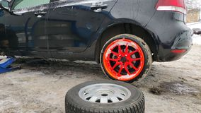 Winter tire fitting on the street. Wheel service, Tire repair, and changing summer to winter tires. Black car lifted on jack. Summer tires in winter.Orange royalty free stock photography